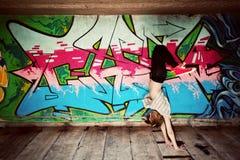 一个舞蹈姿势的时髦的女孩对街道画墙壁 图库摄影