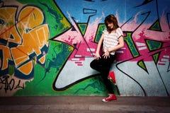 一个舞蹈姿势的时髦的女孩对街道画墙壁 免版税库存图片