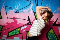 一个舞蹈姿势的时髦的女孩对街道画墙壁 免版税图库摄影