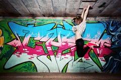 一个舞蹈姿势的时髦的女孩对街道画墙壁 库存图片