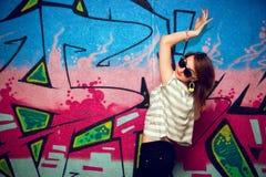 一个舞蹈姿势的时髦的女孩对街道画墙壁 库存照片