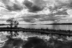 一个船坞在一个湖,有与白色的美丽,深天空的覆盖r 图库摄影