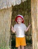 一个芦苇小屋的兴奋小男孩 库存照片