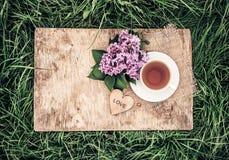 一个芬芳丁香杯子红茶和花在一个老木板的 庭院茶 葡萄酒设色 免版税库存照片