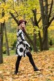 一个花卉被仿造的外套和葡萄酒红帽子的妇女在公园,由河 愉快的女孩,夫人五颜六色的秋天森林画象  库存照片