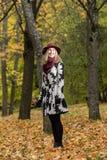 一个花卉被仿造的外套和葡萄酒红帽子的妇女在公园,由河 愉快的女孩,夫人五颜六色的秋天森林画象  免版税库存照片