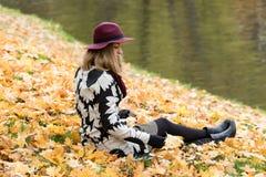 一个花卉被仿造的外套和葡萄酒红帽子的妇女在公园,由河 愉快的女孩,夫人五颜六色的秋天森林画象  库存图片