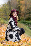 一个花卉被仿造的外套和葡萄酒红帽子的妇女在公园,由河 愉快的女孩,夫人五颜六色的秋天森林画象  图库摄影