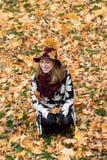 一个花卉被仿造的外套和葡萄酒红帽子的妇女在公园,由河 愉快的女孩,夫人五颜六色的秋天森林画象  免版税库存图片