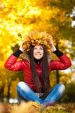 一个花圈的快乐的女孩与秋天生叶 库存图片