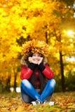 一个花圈的愉快的快乐的妇女与秋天生叶 库存照片