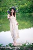 一个花圈的赤足女孩在河附近 库存图片