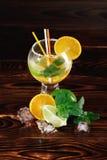 一个花梢鸡尾酒的五颜六色的构成 切的柑橘水果和玻璃有很多在桌背景的冷的酒精 免版税库存照片
