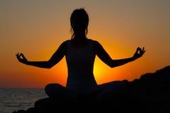 一个苗条健身女孩的剪影在阳光下日落或日出的在莲花姿势 免版税库存照片