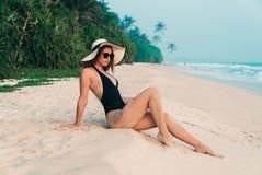 一个苗条女孩基于不与棕榈树和热带密林的一个白色空的海滩,穿戴在黑泳装 库存照片