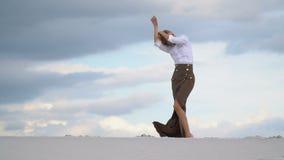 一个苗条女孩站立在沙丘顶部 影视素材