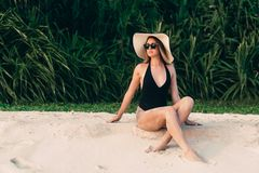 一个苗条年轻美丽的女孩在a坐白色沙子在热带植物附近,享受放松,晒日光浴,穿戴 免版税库存照片