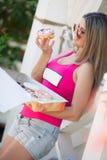 一个苗条金发碧眼的女人的画象用一个甜多福饼 免版税库存图片