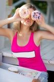 一个苗条金发碧眼的女人的画象用一个甜多福饼 免版税图库摄影