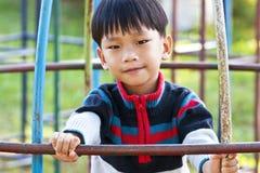 一个英俊的亚洲孩子在操场 免版税库存图片