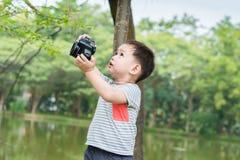 一个英俊的亚洲孩子由DSLR照相机拍照片 图库摄影