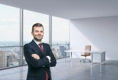 一个英俊的人在一个工作场所在现代壁角全景办公室在纽约,曼哈顿 财政咨询的概念 免版税库存照片