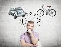 一个英俊的人尝试选择了旅行或通勤的最适当的方式 画汽车和自行车的两个剪影 免版税库存图片