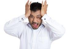 一个英俊的人有一坏天在工作,懊恼与叫喊他的上司大声看照相机 免版税库存照片