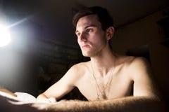 一个英俊的人的画象有赤裸躯干的 一个从灯的特写镜头在一个暗室和光的照片 柔光 绿眼的增殖比 免版税库存图片
