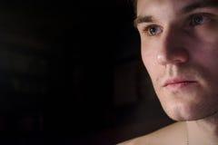 一个英俊的人的画象有赤裸躯干的 一个从灯的特写镜头在一个暗室和光的照片 柔光 绿眼的增殖比 库存照片
