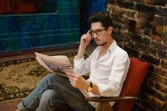 一个英俊的人读一张报纸 免版税图库摄影