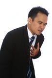 一个英俊的可爱的年轻亚洲商人的照片图象在痛苦中的拿着他的心脏 免版税库存图片
