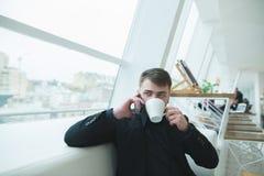 一个英俊的商人在一家现代餐馆坐并且谈话在电话 午餐咖啡的断裂 库存图片