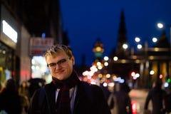一个英俊的年轻人在城市在晚上 免版税库存照片