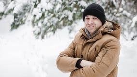 一个英俊的年轻人的画象一件红色夹克的在冬天森林人横渡了他的横跨他的胸口的胳膊 免版税库存图片