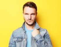 一个英俊的年轻人的画象,时装模特儿 摆在黄色墙壁 免版税图库摄影