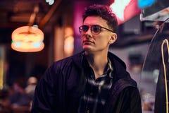 一个英俊的年轻人身分在街道的晚上 有启发性牌,氖,光 库存照片