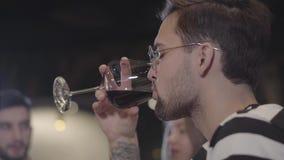 一个英俊的年轻有胡子的人的画象戴品酒眼镜的 喝从在昂贵的一个酒杯的人 股票视频