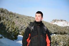 一个英俊的微笑的人的画象冬天山的 库存图片