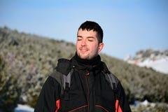 一个英俊的微笑的人的画象冬天山的 免版税图库摄影