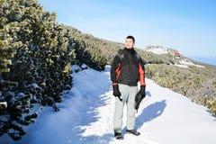 一个英俊的微笑的人的画象冬天山的 库存照片
