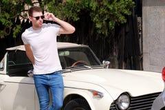 一个英俊的微笑的人,其次摆在都市城市街道他的汽车的男性模型的画象有太阳镜的 免版税库存图片