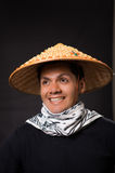一个英俊的微笑的西班牙年轻企业人的画象在黑背景中的戴一个亚洲圆锥形帽子 免版税库存照片