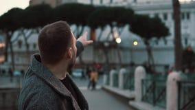 一个英俊的旅游人在罗马的中心的考虑罗马视域在意大利晚上和指向 股票录像