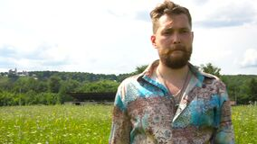 一个英俊的有胡子的人在单独草甸附近走 影视素材