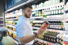 一个英俊的有胡子的人在超级市场选择啤酒 买家在超级市场买酒精 图库摄影