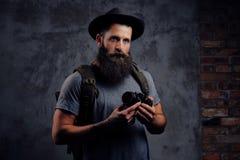 一个英俊的有胡子的旅客的画象一个帽子的有背包和被刺字的胳膊的,举行一台照片照相机,在a 免版税库存照片