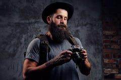 一个英俊的有胡子的旅客的画象一个帽子的有背包和被刺字的胳膊的,举行一台照片照相机,在a 库存图片