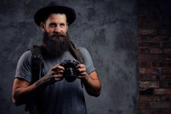 一个英俊的有胡子的旅客的画象一个帽子的有背包和被刺字的胳膊的,举行一台照片照相机,在a 免版税库存图片