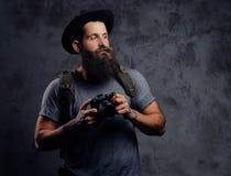 一个英俊的有胡子的旅客的画象一个帽子的有背包和被刺字的胳膊的,举行一台照片照相机,在a 免版税图库摄影